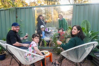 Laura Russo and Andrew Nicholson with their daughter Sigrid and, behind the transparent fence, their neighbours Leo Coyte and Kylie Banyard and sons Wes and Hal.