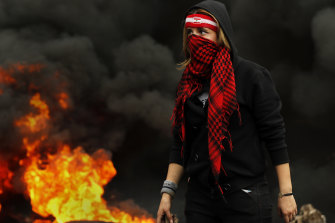 A protester walks past a blockade  of a main highway in the town of Zouk Mosbeh, north of Beirut, Lebanon, on Monday.