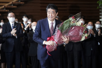 Shinzo Abe receives a bouquet of flowers before leaving the prime minister's office  on Wednesday.