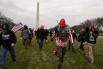 People march with those who claim they are members of the Proud Boys as they attend a rally in Washington.