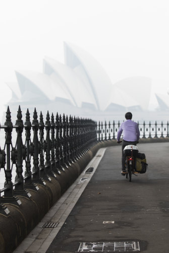 A cyclist rides by Sydney Harbour with the Opera House barely visible in the distance.