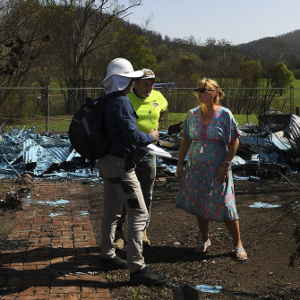 Kim McDonald talks with a NSW Public Works employee and a specialist in asbestos about the cleanup after her home was destroyed.