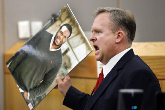 Assistant District Attorney Jason Hermus waves a photo of Botham Jean at the jury during the trial.