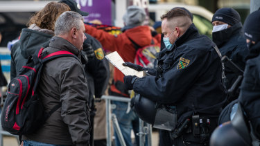 Police officers register one protester at a rally against coronavirus lockdown measures in Leipzig, Germany.