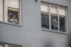 Some of the refugees and asylum seekers detained at the Mantra Hotel in Preston watch a protest on the weekend from a window.