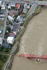 Surging waters from the Chikuma River in Ueda, Nagano Prefecture threaten homes in central Japan.