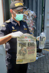 Indonesian Customs offical Dhion Priharyanto holds up a copy of an Australian newspaper among other rubbish in a rejected container.