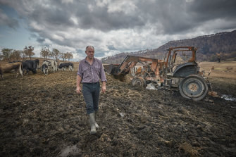 Farmer Farran Terlich walks past the burnt out remains of a tractor he used to fight the bushfire on his farm.