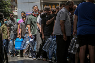 People wait in line at a petrol station in Beirut amid fuel shortages.