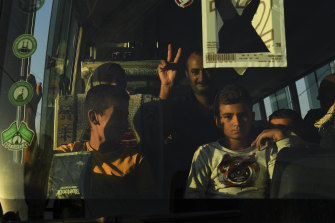 A man makes the peace sign from a minibus laden with refugees from Syria.