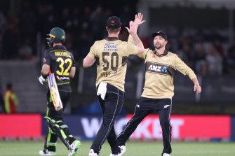 New Zealand's Jimmy Neesham and Devon Conway celebrate after Neesham's catch to dismiss Glenn Maxwell.