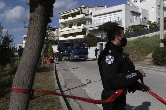 A police truck carries the car of veteran Greek crime reporter Giorgos Karaivaz, who was gunned down in southern Athens.