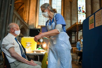 An English patient receives a dose of the Pfizer vaccine inside Salisbury Cathedral