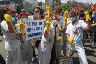 """Yellow gloves: Medical staff hold a placard reading """"there is no magical medical staff"""" during a demonstration in Paris last week, referring to President Emmanuel Macron who said """"there is no magical money for hospitals""""."""