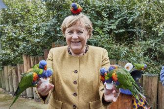 Soon-to-retire German chancellor Angela Merkel, feeding Australian lorikeets at a park in Marlow, Germany, Thursday September 23, 2021.