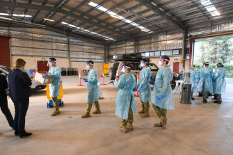 Boots on the ground: ADF personnel perform COVID-19 testing at the Shepparton showgrounds.