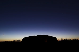 The Saturday sun rises over Uluru, the first morning after the climb was permanently closed.