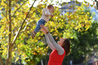 Taking flight: Molly Fleck with 14-month-old son TJ in Surry Hills on Saturday. The family will relocate to the US because of Australia's travel ban.