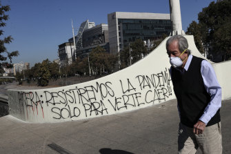 "A man wearing a face mask walks past graffiti against Chilean President Sebastian Piñera that reads in Spanish ""Piñera, we will resist the pandemic just to see you fall!"" in Santiago."