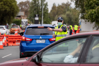 Victoria Police stop motorists entering the state from NSW at Albury on Friday.