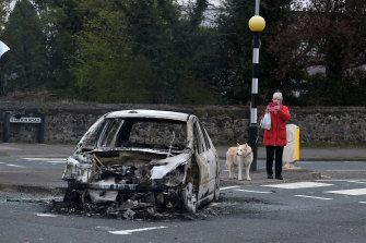 A woman takes a photograph of a burnt-out car at Cloughfern, following  loyalist violence in Belfast, Northern Ireland.