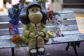 Flower tributes rest next to a statue of Mafalda in Buenos Aires after the death of Quino, her creator.