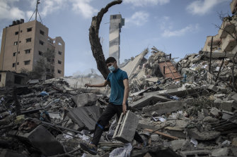 A Palestinian man inspects the damage after a six-storey building was destroyed by an Israeli air strike in Gaza.