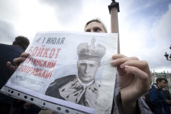 "A woman holds a poster reading ""July 1. Boycott of Putin's amendments"" protesting on Palace Square in St. Petersburg, Russia, on Wednesday."
