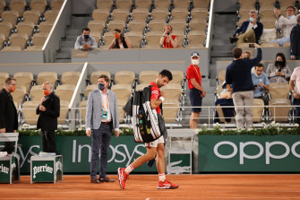 World No.1 Novak Djokovic leaves the court after play was suspended during the fourth set of his French Open quarter-final.
