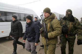 Ukrainian war prisoners escorted by armed Russia-backed separatist soldiers walk to buses to be exchanged at a checkpoint near Horlivka, eastern Ukraine.