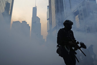 A police officer surrounded by tear gas.