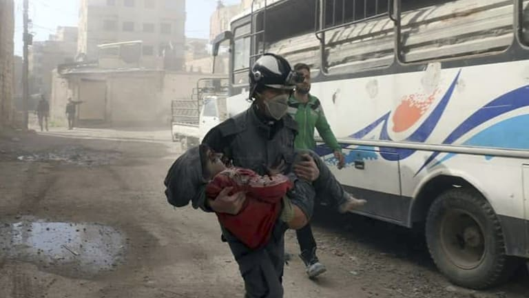 This pictue provided by the Syrian Civil Defence White Helmets shows a member of the Syrian Civil Defence group carrying a boy wounded during airstrikes and shelling by Syrian government forces in Ghouta on Friday.