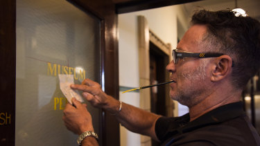 Mr Haines applies gold leaf to the museum's logo on one of the glass doors.