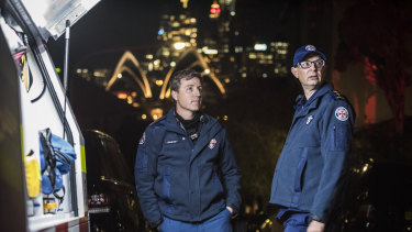 Reverend Paul McFarlane, right, senior chaplain for NSW Ambulance service, speaks with Duty Ops Manager, Andrew Rienits, Special Ops Team Leader, at the scene of a siege in Kirribilli.