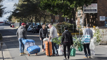 Residents packing up items including a piano from their units in the Mascot Towers Building.