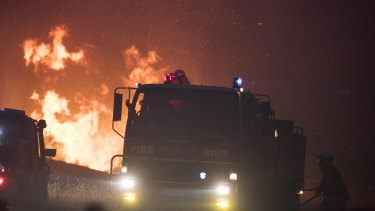 Firefighters work to contain the Pelham Road fire in southern Tasmania on Monday.