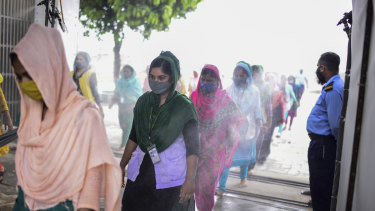 Masked garment workers walk through a disinfection at a factory in Savar, Bangladesh.