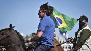 Brazilian President Jair Bolsonaro rides a horse greeting supporters outside the presidential palace in Brasilia on Sunday.