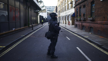 An armed police officer stands guard near the scene.