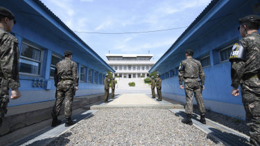 Four North Korean soldiers and four South Korean soldiers stand at the border village of Panmunjom in the Demilitarized Zone.
