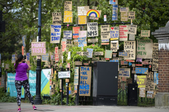 A woman takes a photo in-front of signs in support of the NHS and key workers in East London on Saturday in London, England.