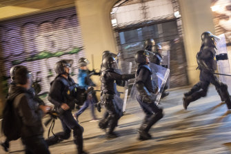 National police officers run behind demonstrators during a protest in Barcelona ahead of Sunday's general election.