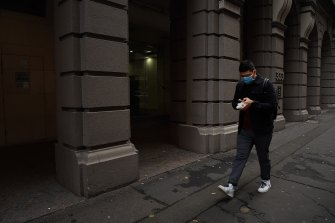 A man wearing a face mask walks along Kent street in the Sydney CBD.