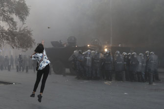 An anti-government protester throws a stone towards riot police during a protest near Parliament Square, Beirut, Lebanon, on Tuesday.