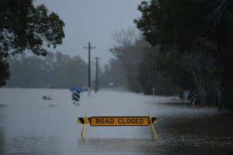 A road closed sign stands in floodwaters on the Coolangatta Road at Far Meadow in the Shoalhaven area.