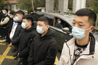Peter Daszak of the World Health Organization leaves in a car past a row of security personnel at the Hubei Centre for Disease Control and Prevention in Wuhan.
