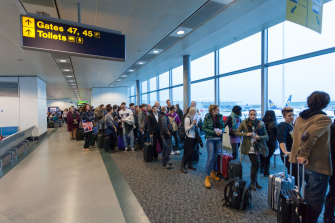 Air passengers queued up waiting in a London airport.
