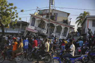 People gather outside the Petit Pas Hotel, destroyed by the earthquake in Les Cayes, Haiti by a 7.2 magnitude earthquake.