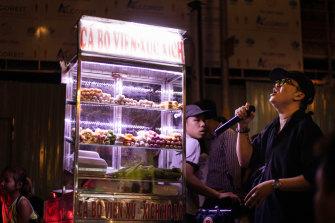 A street vendor passes a karaoke singer on Bui Vien Street, Ho Chi Minh, Vietnam.
