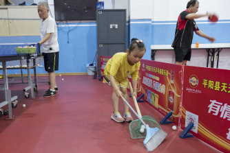 A young girl at the Tiantianle Table Tennis Club collects balls after training on Friday.